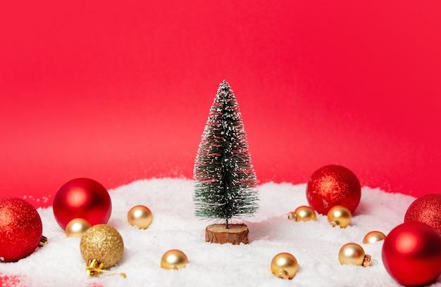 Kerstboom met rond snuisterijen en sneeuw