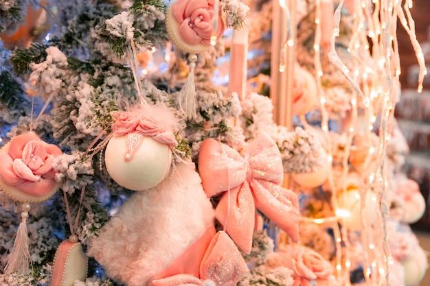 Kerstboom met roze decor en lichten, garland close-up. kerstdecoratie, nieuwjaar. winter vakantie feest