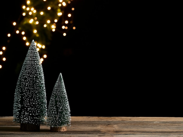 Kerstboom met sneeuw op houten tafel tegen donkere achtergrond, bokeh effect, ruimte voor tekst