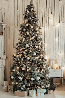 Kerstboom met witte ballen en slingers met houten rustieke witte muur