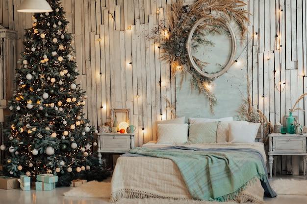 Kerstboom met witte ballen en slingers.
