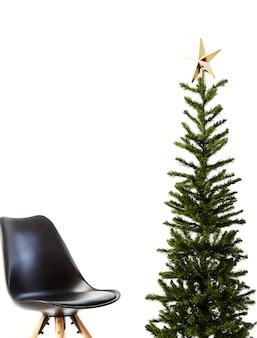 Kerstboom met zwarte stoel