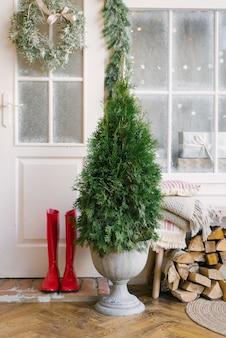 Kerstboom of thuja bij de toegangsdeur naar het huis, rode laarzen en hout voor de open haard