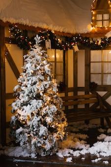 Kerstboom onder de sneeuw op de binnenplaats van het huis. fotozone in de fotostudio