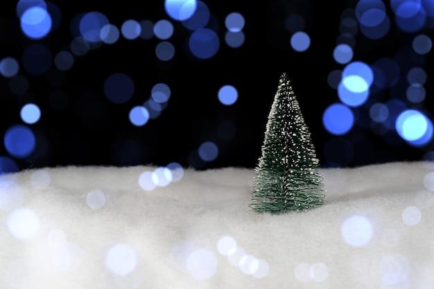 Kerstboom op de voorgrond en onscherpe lichten op de achtergrond.
