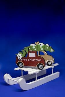 Kerstboom op houten slee, de vieringsconcept van de kerstmisvakantie. merry christmas wenskaart.