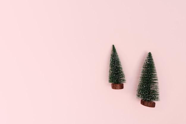 Kerstboom op roze achtergrond. kerstmis, winter, nieuwjaar concept. plat lag, bovenaanzicht