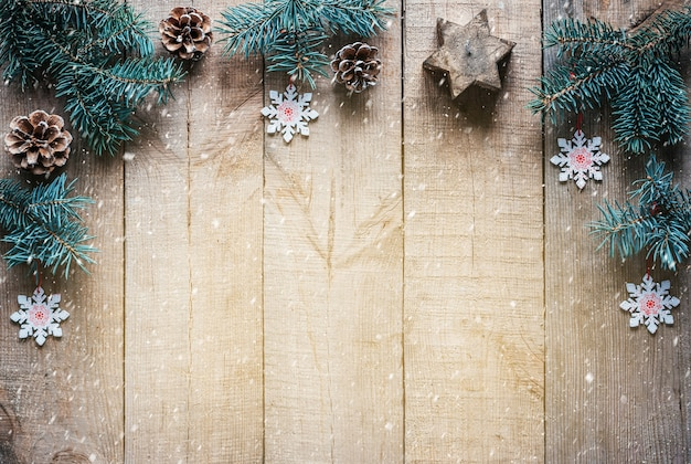 Kerstboom takken dennenappels snoflakes en kaars ster op houten achtergrond