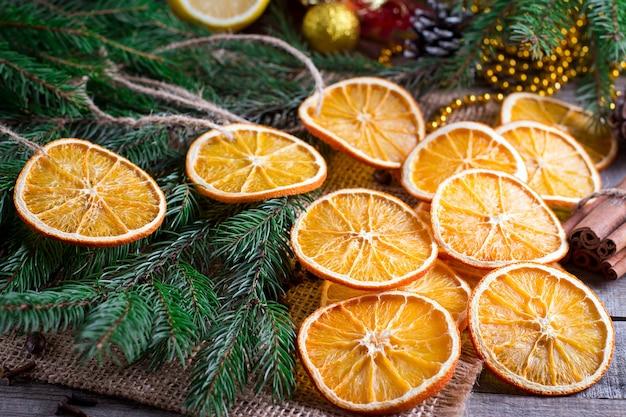 Kerstboom van droge sinaasappelen, kaneel en anijsplantsterren op houten rustieke lijst en spar op achtergrond