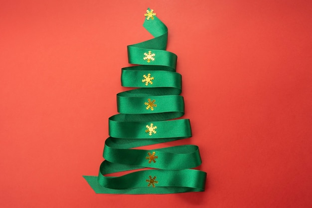 Kerstboom van groene linttape op rode achtergrond