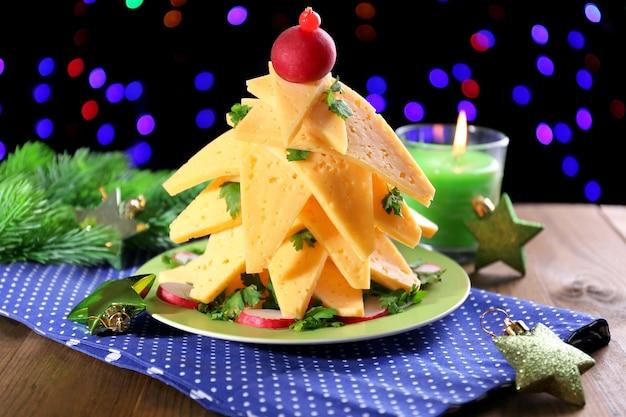 Kerstboom van kaas op tafel op donker