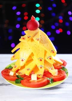 Kerstboom van kaas op tafel op donkere achtergrond
