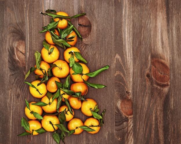 Kerstboom van mandarijnen op donker hout