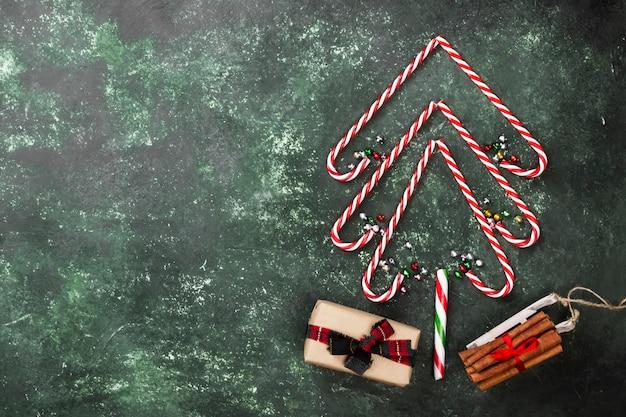 Kerstboom van snoep stokken en doos met cadeau op een groene ondergrond