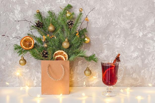 Kerstboom versierd gouden ballen, kegels in ambachtelijk pakket, lichtenslinger en glas warme glühwein met kruiden op tafel.