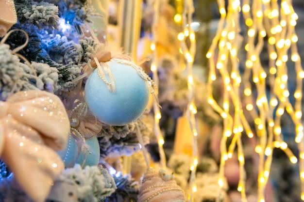 Kerstboom versierd met blauwe ballen en lichten, garland close-up. xmas decor, nieuwjaar. winter vakantie feest