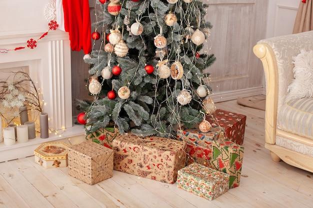 Kerstboom versierd met geschenken, open haard en kaarsen