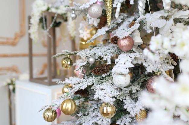 Kerstboom versierd met gouden en roze ballen met speelgoed en decoratieve sneeuw close-up