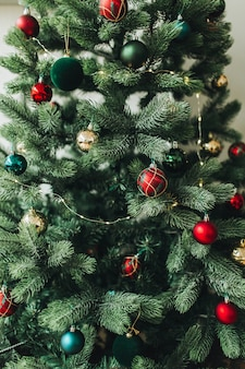Kerstboom versierd met prachtig rood, goud, groen speelgoed, ballen en slinger