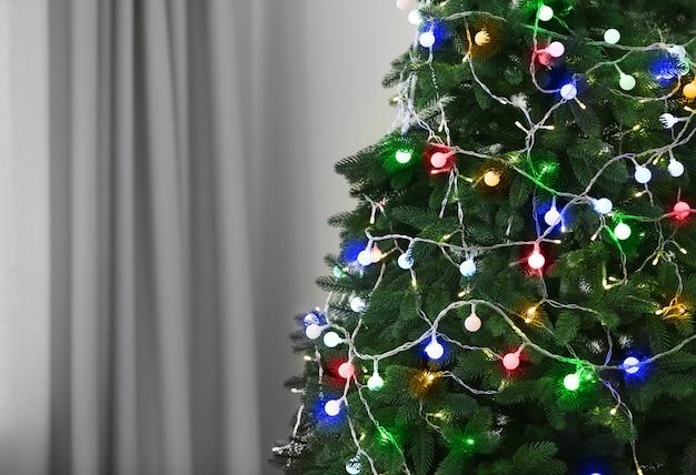 Kerstboom versierd met slingers in de kamer