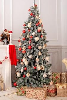Kerstboom versierd met speelgoed en ballen in huis