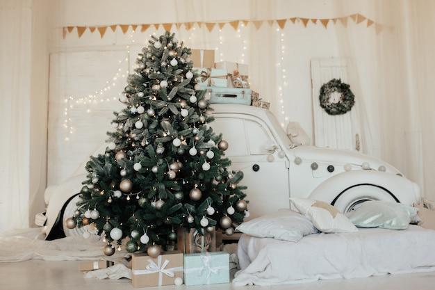 Kerstboom versierd met witte ballen en slingers. witte auto dichtbij kerstboom.