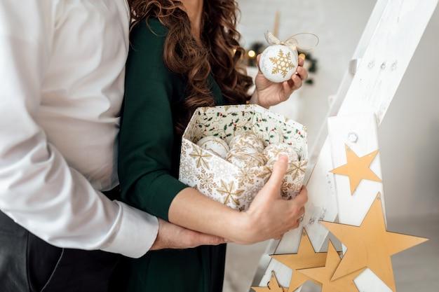 Kerstboom versieren. vrouw en echtgenoot die een doos met kerstmisspeelgoed houden in skandinavische stijl. close-upfoto van handen.