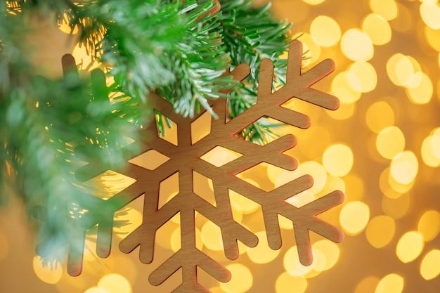 Kerstboomachtergrond en kerstmisdecoratie met sneeuwvlok op gouden bokehachtergrond