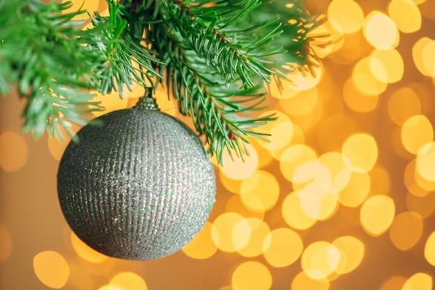Kerstboomachtergrond met gouden snuisterij bij bokeh het fonkelen