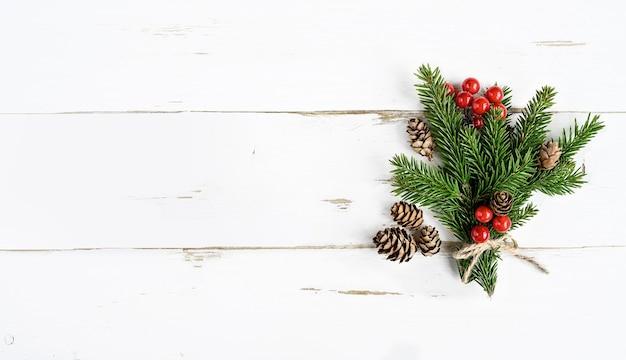 Kerstboombos, kegels en rode bessen op witte houten achtergrond.