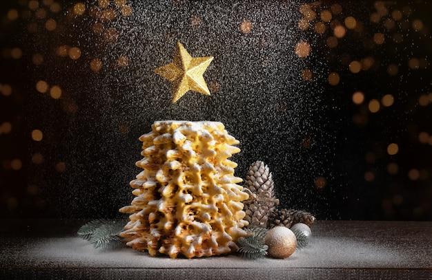 Kerstboomcake met een ster en dalende poedersuiker. kerst cake op een houten tafel versierd.