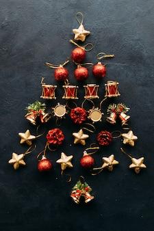 Kerstboomdecoratie gemaakt van speelgoed op blauwe muur.