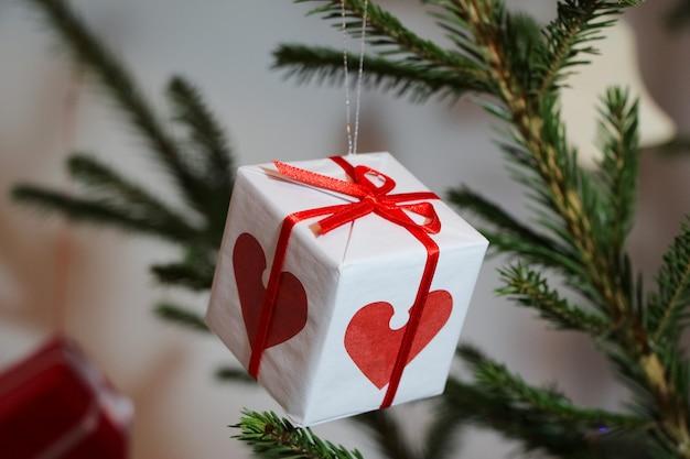 Kerstboomdecoratie in de vorm van een kleine geschenkdoos van witte kleur met een rood lint