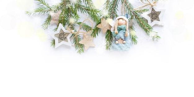 Kerstboomdecoratie met sterren en engel in de sneeuw