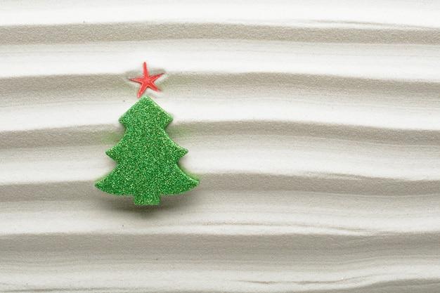 Kerstboomdecoratie op gestructureerd strandzand met geribbelde lijnen en kopieer ruimte voor een leuke zomerse seizoensgroet