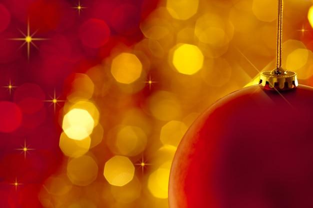 Kerstboomdecoratie op lichten rode en gouden achtergrond