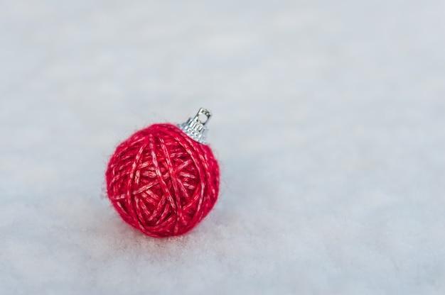 Kerstboomdecoratie van rode garenbal op natuurlijke sneeuw wordt gemaakt die