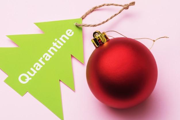 Kerstboomspeelgoed en tag met tekst op een roze achtergrond concept over quarantaine voor de nieuwjaarsvakantie