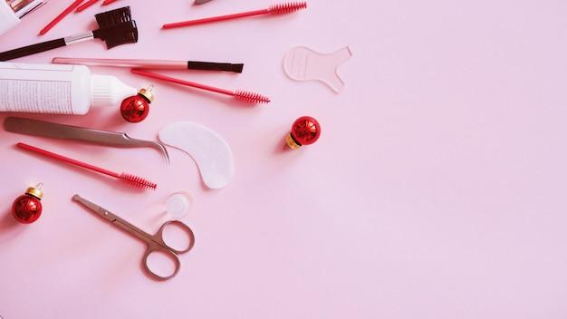 Kerstboomspeelgoed met hulpmiddelen voor behandeling op roze, plat leggen