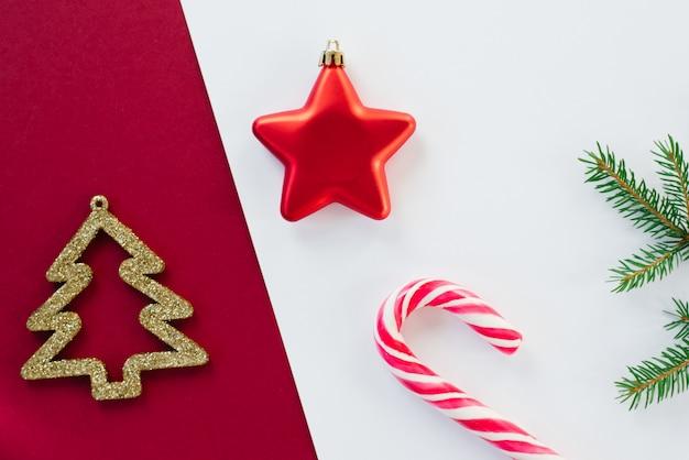 Kerstboomspeelgoed, rode ster en gouden kerstboom, lollyriet en nette tak op wit en bourgondië
