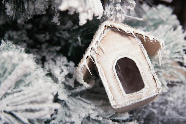 Kerstboomstuk speelgoed op kerstboomclose-up. nieuwjaar papier speelgoed huis. papieren beeldje huis