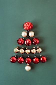 Kerstboomsymbool gemaakt van rode en gouden kerstballen ballen op groen