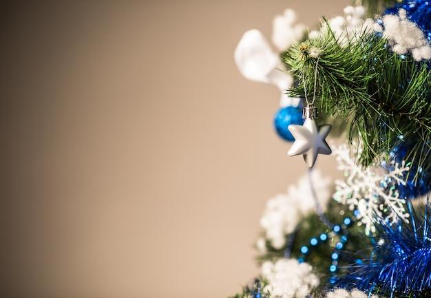 Kerstboomtak close-up met speelgoed op een bruin oppervlak