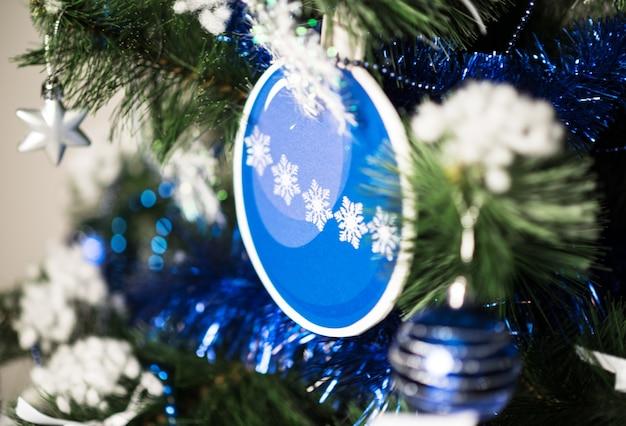 Kerstboomtak close-up met speelgoed op een bruine achtergrond.
