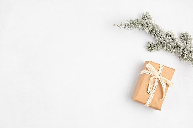 Kerstboomtak en geschenkdoos verpakt in biologisch ambachtelijk papier, plat leggen, bovenaanzicht