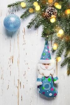 Kerstboomtak met blauw speelgoed op witte houten achtergrond.