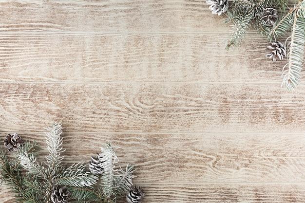 Kerstboomtak met dennenappels op rustieke houten tafel. winter achtergrond met kopie ruimte. bovenaanzicht. plat leggen