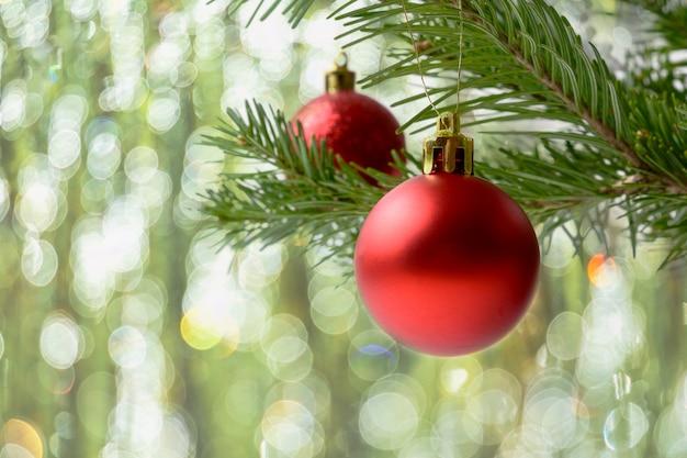 Kerstboomtak met rood ornament en bokeh