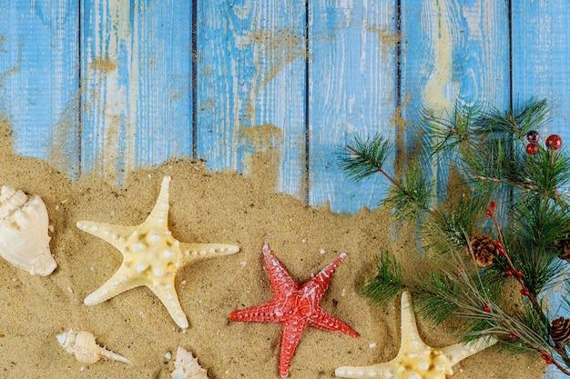 Kerstboomtak over zandstrand met zeeschelpen en zeester op een blauwe houten achtergrond