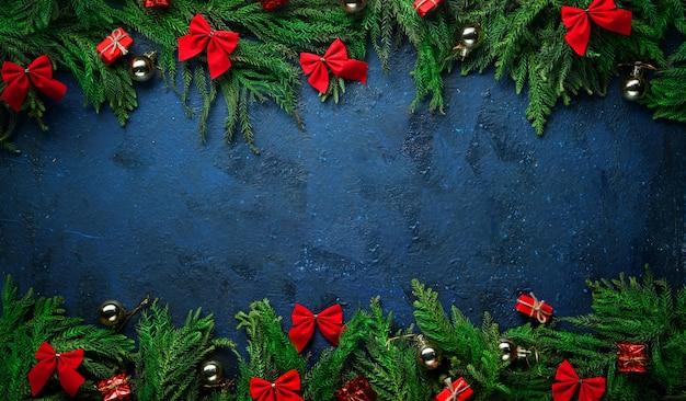 Kerstboomtakken en decoratie aan boven- en onderkant. banner donkerblauwe achtergrond kopie ruimte.